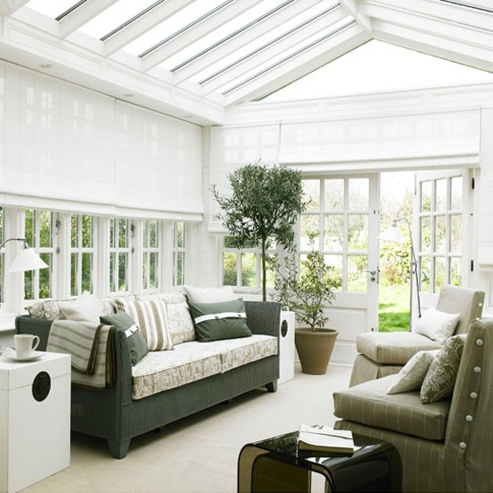 Conservatory-living-area-painted-white-with-potted-plants-and-glass-roof