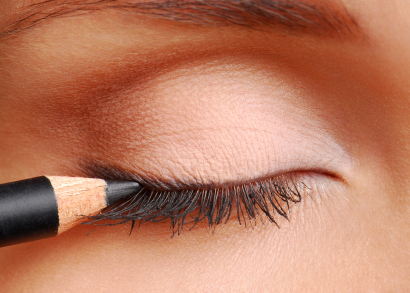 Black cosmetic pencil. Women eyes closed. Long eyelashes.